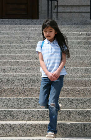 Little girl walking down granite steps outdoors, getting out of school or church building Stok Fotoğraf