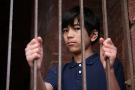 iron bars: Boy standing behind bars, sad  or wary expression Stock Photo