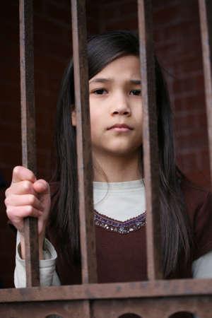 rejas de hierro: Infeliz muchacha de pie detr�s de las rejas de la puerta de la c�rcel o