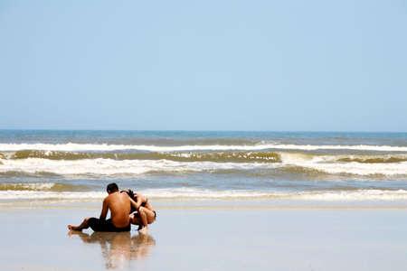 Sad couple sitting dejectedly on beach photo