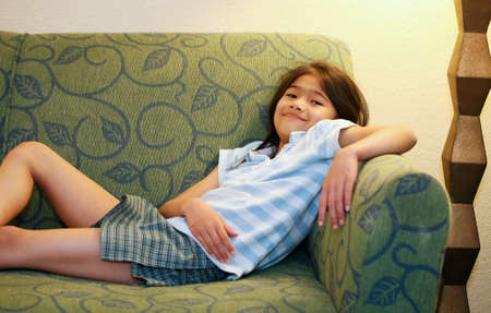 sofa: Little girl relaxing on green couch or sofa