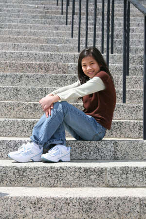 Young girl sitting on large granite stairs outdoors in front of church or school building photo