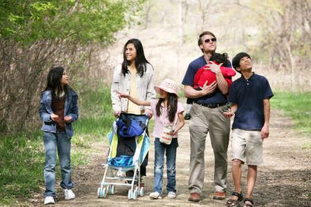 familia de cinco: Familia caminando por sendero tranquilo
