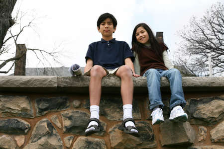 Two children sitting on rock ledge outdoors,  brother and sister