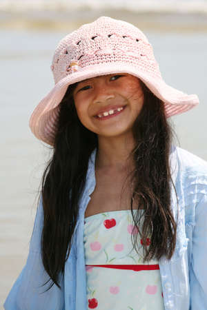 Cute little girl in pink hat at beach
