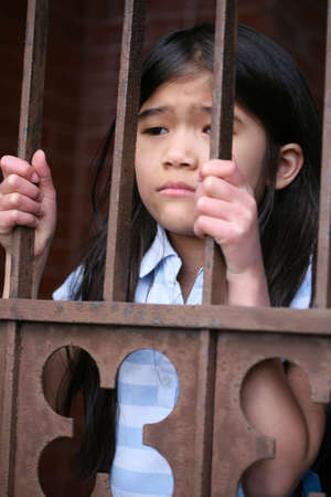 Little girl standing behind iron bars with sad expression, with her looking in or out of gate or prison