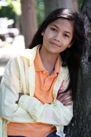 scandinavian descent: Young girl relaxing against tree in summer. Part Thai - Scandinavian descent Stock Photo