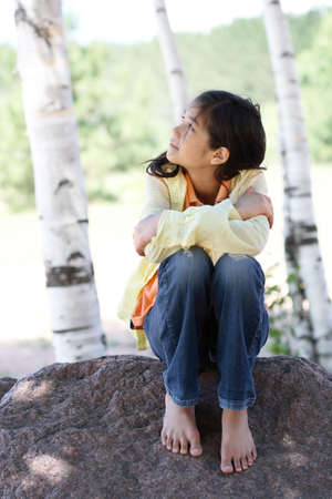Little girl sitting under trees, looking up photo