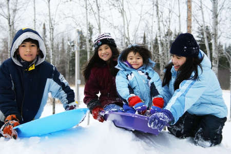 winter woman: Four kids enjoying winter outdoors sledding