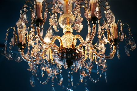 Elegant crystal chandelier hanging against blue background Фото со стока