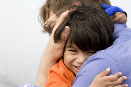Little boy giving his father a big hug Stock Photo