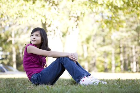 Little girl sitting on grass looking over shoulder photo