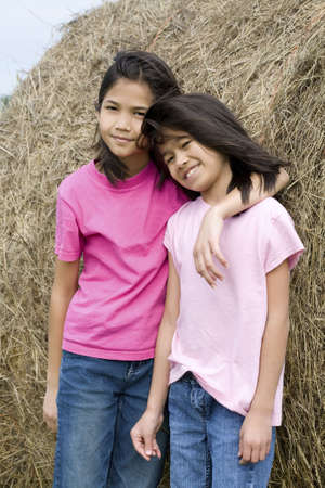 Two young girls standing against haybale Stock Photo - 5811860