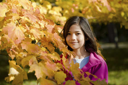 Little biracial asian girl standing amongst bright autumn leaves photo