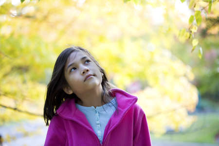 young girl looking up at autumn leaves photo