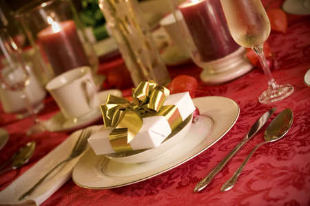 christmas dish: Elegant Christmas table setting in red and gold colors, gift as focal point