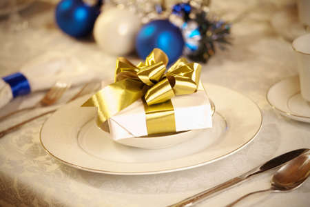 Elegant blue and white Christmas table setting with gold ribbon gift photo