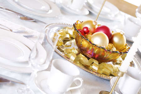 Bowl of red and gold ornaments on table