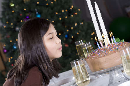Little girl blowing out her birthday cake candles photo