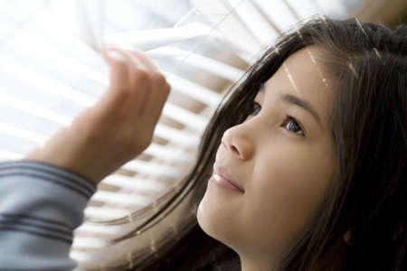Girl looking out window through blinds photo