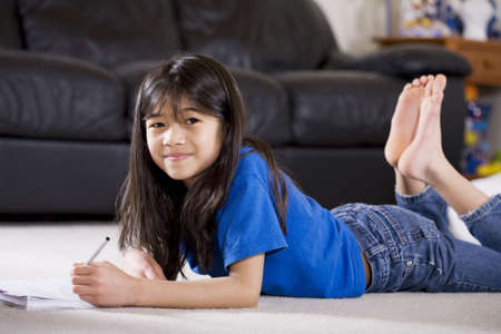 white sofa: Little girl doing her homework
