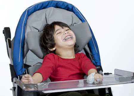 Three year old disabled boy in medical stroller photo