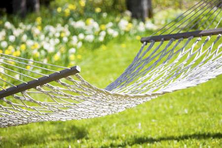 Hammock out on sunny yard near flower garden