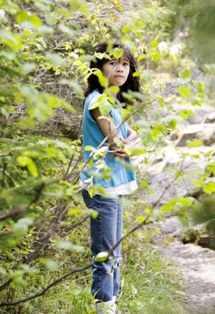 Girl lost in woods, scared, looking around in surprise Stock Photo