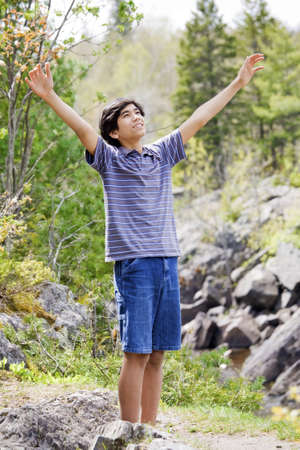 Teenage boy raising hands in praise to God outdoors on mountain photo