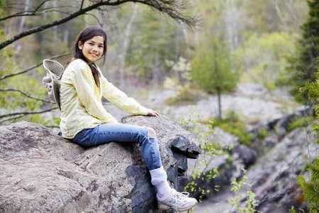 cliff edge: Girl sitting on rock cliff edge over river