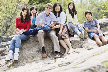 Multiracial Family sitting together on rocky ledge Stock Photo - 7113311