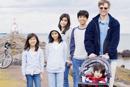 Vader met zijn vijf kinderen op het strand, interracial familie Stockfoto