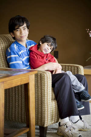 cerebral palsy: Big brother taking care of disabled sibling with cerebral palsy