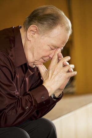 Elderly man praying in dark church Stock Photo