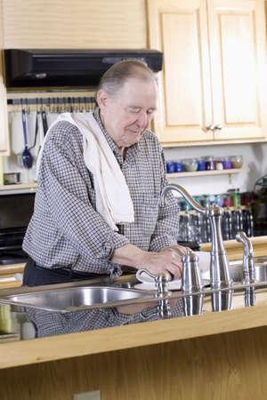 Elderly man washing dishes photo