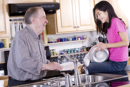 Old man and girl washing dishes photo