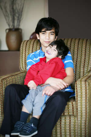 Big brother holding his younger sibling with cerebral palsy photo