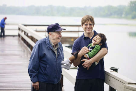 three generations: Three generations interacting together on the dock on misty morning