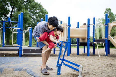 cerebral palsy: Older brother helping disabled sibling play at playground