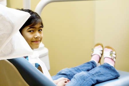 Little Asian girl sitting in dentists chair ready for cleaning photo