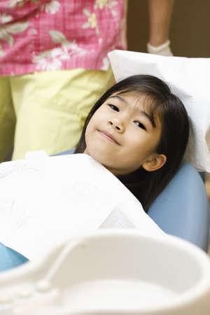 歯医者に座っている小さなアジアの女の子のクリーニングの準備ができて椅子します。 写真素材