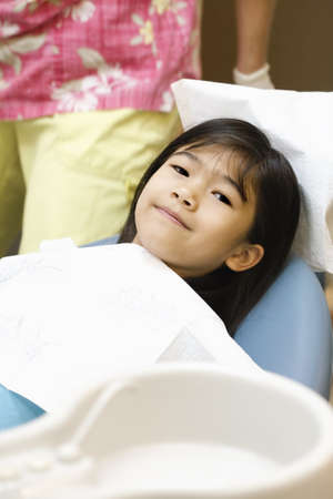 Little Asian girl sitting in dentist's chair ready for cleaning Stock Photo - 8818447