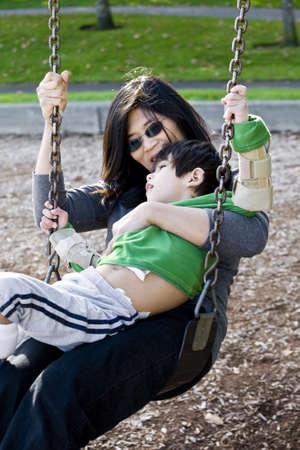 discapacidad: Madre swinging con su hijo con discapacidad con par�lisis cerebral Foto de archivo