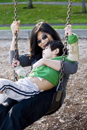 handicapped person: Mother swinging with her disabled son with cerebral palsy Stock Photo
