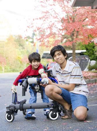 discapacitados: Muchacho adolescente con discapacitados hermano peque�o en walker a caminar