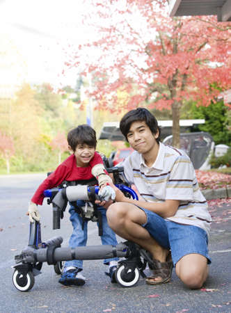 Teen boy with disabled little brother in walker out walking  Banco de Imagens