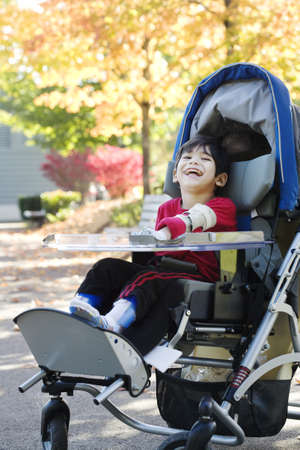 Disabled boy with cerebral palsy in medical stroller enjoying an autumn day outdoors at the park photo