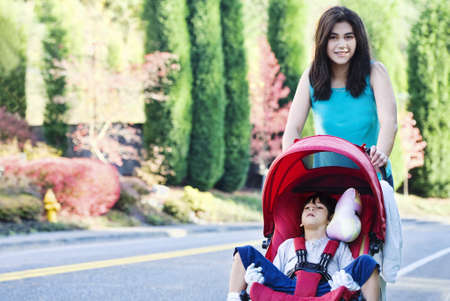 Teen girl pushing her little disabled  brother in stroller outdoors photo