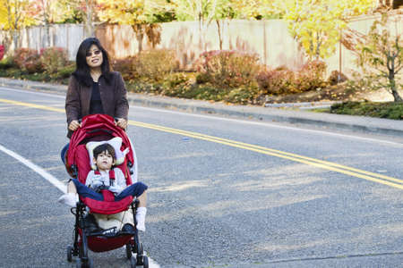 babysit: Mother walking with her disabled son in stroller outdoors