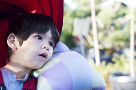 Cute four year old boy looking quietly off to side while sitting in stroller